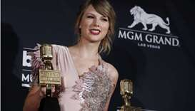 Taylor Swift holds her awards for Top Female Artist and Top Selling Album.
