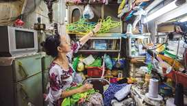 Nguyen Thi Kim Ngoc arranges cloth-hangers in her 6.7sq m home in Ho Chi Minh City.