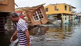 a man walks past destroyed homes in Catano, Puerto Rico