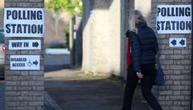 A woman enters a polling station as voting begins in local government elections in London