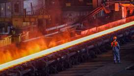 A red-hot steel plate passes through a press at a steel plant