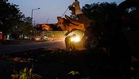 An Indian man chops a tree which fell onto a road during a storm in Agra