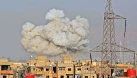 Smoke rises from buildings after regime strikes on the Palestinian camp of Yarmuk and the neighbouri
