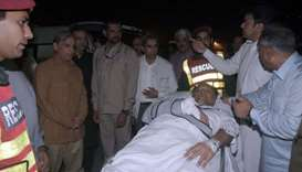 Officers and rescue workers move Pakistan's Interior Minister Ahsan Iqbal on a stretcher, after he w