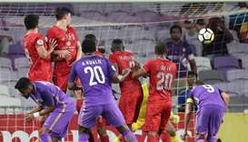 Al-Duhail's players jump to defend as Al-Ain's Ahmed Khalil scores