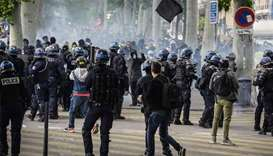 French anti-riot police officers face protesters dressed in black and holding a black flag during an