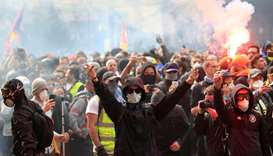 Masked protesters react during clashes with riot police as part of the traditional May Day labour un