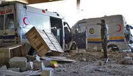 A Syrian government soldier stands past destroyed ambulances and vehicles of the Syrian Civil Defenc