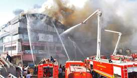 Indian firefighters try to control a major fire in a building housing a college, in Surat