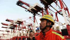 A port worker monitors the unloading of containers on to trucks at the port of Qingdao in northeast