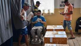 People vote during the European elections and a referendum at a polling station in Comana