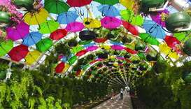 A colourful floral and umbrella arch at the Corniche metro station has become a major attraction alo