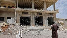 A man stares at a building damaged during reported shelling by government and allied forces, in the