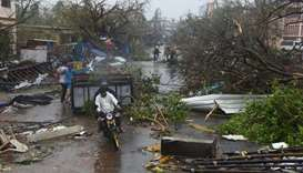 People move through debris on a road after Cyclone Fani hit Puri, in the eastern state of Odisha, In