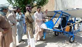 Pakistani villager Muhammad Fayyaz (R) speaks to visitors as he stands alongside his small plane at
