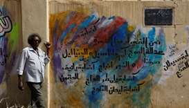 Rashid Drar poses next to a graffiti of him near the defence ministry compound in Khartoum