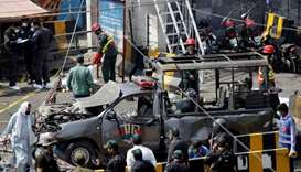 Police officers survey while rescue workers attend to a body at the site of a blast in Lahore, Pakis