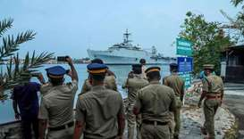 Indian Navy personnel watch and take photos as the INS Jalashwa ship enters the Cochin port carrying