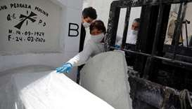 A woman touches the coffin holding the body of a person who died of the coronavirus disease, before