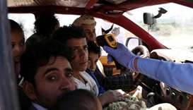 A health worker takes the temperature of people riding a taxi van, amid concerns of the spread of th