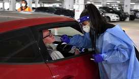 Medical staff perform a test for the coronavirus at a drive-through testing site in a Melbourne carp