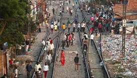Local residents stand on railway tracks outside their homes during an extended nationwide lockdown t