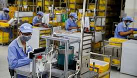 Employees wearing face masks work at a factory of the component maker SMC during a government organi