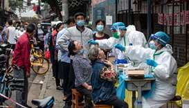 Medical workers take swab samples from residents to be tested for the coronavirus in a street in Wuh
