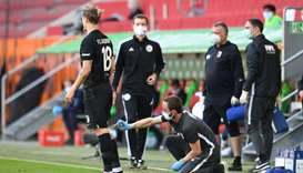 Augsburg's Croation defender Tin Jedvaj (L) receives medical attention during the German first divis