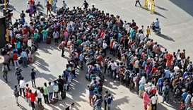 Migrant workers and their families gather to get on buses to reach to a railway station to board tra