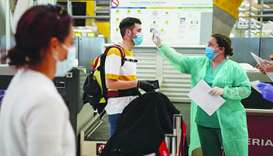 A medical worker checks the temperatures of a passenger at the check-in counters inside the departur