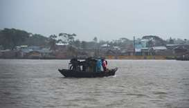 People cross a river on a boat ahead of the expected landfall of cyclone Amphan, in Khulna