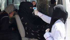 A health worker takes temperature of passengers of a van, amid fear of coronavirus disease, on the o