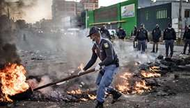 A South African police officer removes a burning barricade outside the Booysens informal settlement,