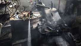 Firefighters spray water on the wreckage of a Pakistan International Airlines aircraft after it cras