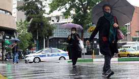 Iranians wear protective face masks, following the outbreak of the coronavirus disease, as they walk
