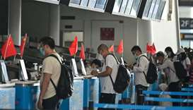 Passengers wearing face masks are seen at airline counters at Tianhe airport in Wuhan, in China's ce