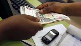 A customer conducts a mobile money transfer, known as M-Pesa, inside the Safaricom mobile phone care