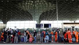 Passengers wearing protective face masks wait in a queue to enter Chhatrapati Shivaji International
