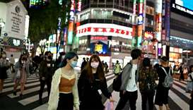 People wearing face masks cross a street in Tokyo's Shinjuku area