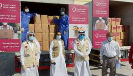 FOOD KITS: Qatar Charity handing over food kits to BCQ through MoI and MADLSA at a school premise.