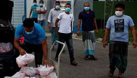 Migrant workers living in a factory-converted dormitory collect meals donated by charities for their