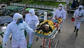 Health personnel of a medical emergency response service carry Brazilian Eladio Lopes, 79, -infected