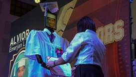 A diploma is attached to a robots, with a graduating student picture shown on a tablet, as the first