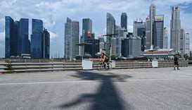 A cyclist rides past buildings in the financial business district (background) in Singapore.