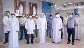 The son of an 88-year-old Qatari man who recovered from Covid-19 is seen with the medical staff of H