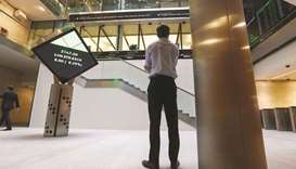 A visitor looks at a ticker of share prices inside the London Stock Exchange (file). The FTSE 100 cl