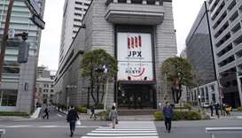Pedestrians walk by the Tokyo Stock Exchange building. The Nikkei 225 closed down 0.2% to 21,877.89
