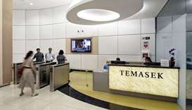 Signage for Temasek Holdings is displayed in the lobby at the company's headquarters as employees pa