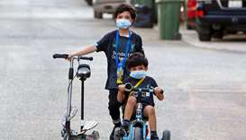 Kuwaiti children, wearing protective facemasks due to the coronavirus pandemic, cycle in a street in